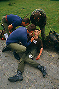 A boy soldier collapses on the ground suffering fatigue and dehydration on the rigorous 10-mile march conducted as a squad, over undulatiing terrain with each candidate carrying a bergen (back pack) weighing 35 pounds.(plus water) and a weapon. Three senior trainers help revive the lad with smelling salts who fell under the weight of his backpack and weapon carried on a hot day and without drinking enough fluids. The march must be completed in 1 hour and 50 minutes. This forms part of the 14-week long Pegasus (P) Company selection programme. Recruits wanting to join the British Army's Parachute Regiment held regularly at Catterick army barracks, Yorkshire need to pass this and other tests before earning the right to wear the esteemed maroon beret.