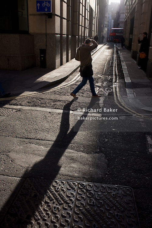 A businessmen squints into winter sunlight on the corner of Lombard Street and Abchurch Lane, EC4, in the City of London.