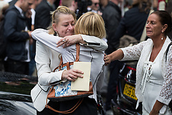 "© Licensed to London News Pictures . 28/08/2015 . Salford , UK . Mourners hug outside the church after the service . The funeral of Paul Massey at St Paul's CE Church in Salford . Massey , known as Salford's "" Mr Big "" , was shot dead at his home in Salford last month . Photo credit : Joel Goodman/LNP"
