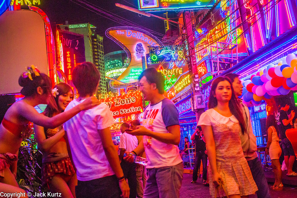 """12 JANUARY 2013 - BANGKOK, THAILAND:  Ladyboy (transgendered) entertainers flirt with customers they try to draw into the Cockatoo bar in the Soi Cowboy red light district in Bangkok. In Thai, the ladyboys are called kathoey. Many work in the entertainment and night life sectors of the Thai economy. Prostitution in Thailand is illegal, although in practice it is tolerated and partly regulated. Prostitution is practiced openly throughout the country. The number of prostitutes is difficult to determine, estimates vary widely. Since the Vietnam War, Thailand has gained international notoriety among travelers from many countries as a sex tourism destination. One estimate published in 2003 placed the trade at US$ 4.3 billion per year or about three percent of the Thai economy. It has been suggested that at least 10% of tourist dollars may be spent on the sex trade. According to a 2001 report by the World Health Organisation: """"There are between 150,000 and 200,000 sex workers (in Thailand).""""    PHOTO BY JACK KURTZ"""