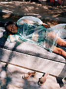A woman sleeps in a plastic raincoat on Pattaya's beach promenade.