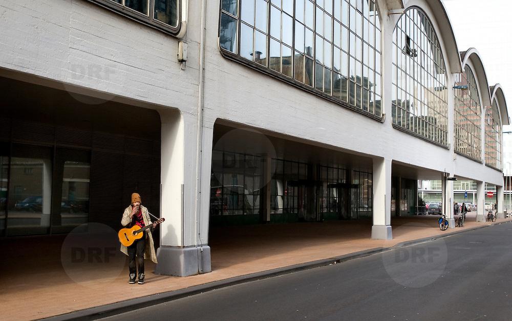 Nederland Rotterdam 2 maart 2008 20080302 .Zwerver daloze met gitaar voor Cruise Terminal op Kop van Zuid ..Foto David Rozing
