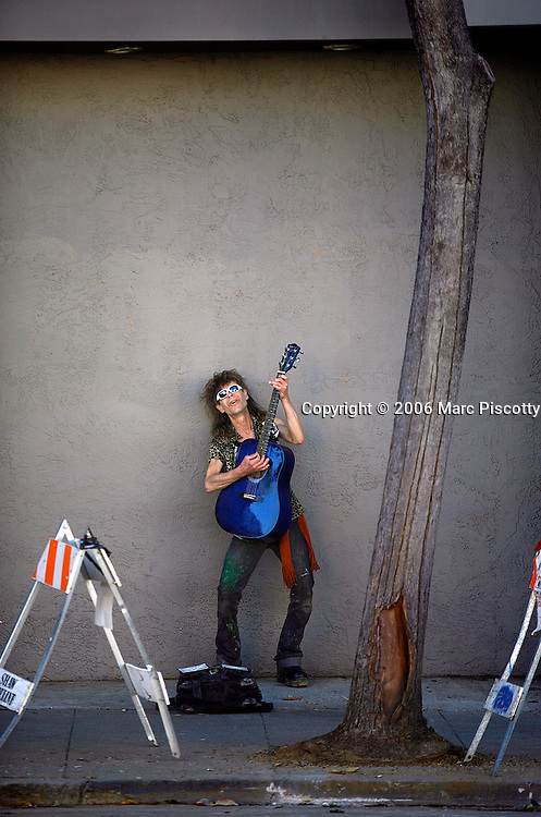 """SHOT 10/23/2007 - A street performer sings with a guitar on Valencia Street in the Mission District of San Francisco, Ca. one afternoon. The Mission District, also commonly called """"The Mission"""", is a neighborhood in San Francisco, California, USA named after the sixth Alta California mission, Mission San Francisco de Asis. The neighborhood is ethnically and economically diverse, with a population that is half Latino, a third White, and 11 percent Asian. The Inner Mission was viewed as a Hispanic neighborhood through much of the 1960s and 1970s. However, the Mission today is both the nexus of the Chicano and Latino community and a neighborhood of artists and hipsters. The City and County of San Francisco is the fourth most populous city in California and the fourteenth-most populous in the United States. San Francisco is a popular international tourist destination renowned for its steep rolling hills, an eclectic mix of Victorian and modern architecture, its large LGBT (lesbian, gay, bisexual, and transgender) population, and its chilly summer fog and mild winters. Famous landmarks include Union Square, Pacific Heights, Russian Hill, Fisherman's Wharf, North Beach and Chinatown..(Photo by Marc Piscotty © 2007)"""