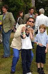 "LORD LINLEY teaching his son the HON.CHARLES ARMSTRONG-JONES how to take photographs at the Goodwood Festival of Speed on 9th July 2006.  Cartier sponsored the ""Style Et Luxe' for vintage cars on the final day of this annual event at Goodwood House, West Sussex and hosted a lunch.<br />