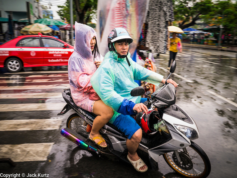 30 MAY 2013 - BANGKOK, THAILAND:  A couple on a motocycle drives through Bobae Market in Bangkok. Bobae Market is a 30 year old famous for fashion wholesale and is now very popular with exporters from around the world. Bobae Tower is next to the market and  advertises itself as having 1,300 stalls under one roof and claims to be the largest garment wholesale center in Thailand.    PHOTO BY JACK KURTZ