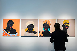 """© Licensed to London News Pictures. 28/10/2020. LONDON, UK.  A visitor at the preview of """"Becoming as well as Being"""", an exhibition of new works by Ghanaian painter Kwesi Botchway, many created during the COVID-19 pandemic lockdown. Curated by Ekow Eshun at the inaugural London space of Gallery 1957, the exhibition runs 28 October to 13 December.  Photo credit: Stephen Chung/LNP"""