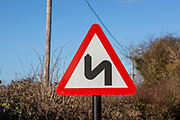 Red triangle road sign warning of sharp corners ahead, UK