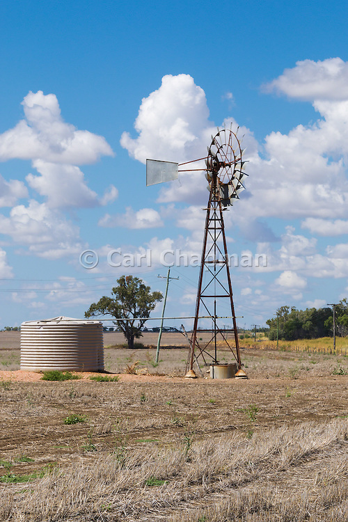 Windmill and water tank in dry cropping farm paddock under cumulus clouds in Clermont, Queensland, Australia. <br /> <br /> Editions:- Open Edition Print / Stock Image