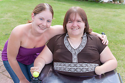 Woman with a disability and her non disabled friend out in the garden,