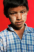 Young boy with Thank on his face, red wall, Shwe Ba Taung caves, Monywa