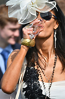 National Hunt Horse Racing - 2019 Randox Health Grand National Festival - Saturday, Day Three (Grand National Day)<br /> <br /> Female fan in hat drinks from a champagne glass at Aintree Racecourse.<br /> <br /> COLORSPORT/WINSTON BYNORTH