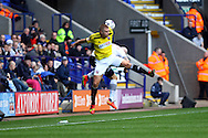 Brentfords' Jake Bidwell jumps for the ball with Bolton Wanderers' Kevin McNaughton. Skybet football league championship match, Bolton Wanderers v Brentford at the Macron stadium in Bolton, Lancs on Saturday 25th October 2014.<br /> pic by Chris Stading, Andrew Orchard sports photography.