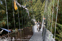 Motorcycle Sherpa's Bear Haughton on his Royal Enfield Himalayan crossing a suspension bridge on the Ride to the Heavens motorcycle adventure in the Himalayas of Nepal. On the fourth day of riding, we went from Kalopani to Muktinath. Thursday, November 7, 2019. Photography ©2019 Michael Lichter.