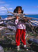 Tlingit girl, Melody Ramos, gathering driftwood for a cooking fire at her family's fishing camp near the mouth of the Situk River souotheast of Yakutat, Alaska.