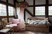Curled up under a duvet on a sofa, a teenager sleeps off a late night, the morning after a birthday party in a countryside barn, on 23rd June 2019, in Kington, Herefordshire, England.