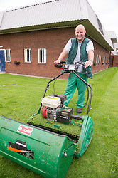 A prisoner mowing the grass outside a cell block