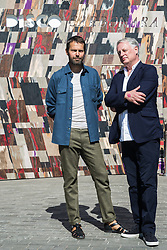 London, UK. 13 September, 2019. Designer Martino Gamper (l) poses with Ben Evans (r), Director of the London Design Festival, in front of his Disco Carbonara installation in Coal Drops Yard, a Festival Commission for the London Design Festival. A 'false facade of a disco with a fresh take on traditional cladding from the Italian Alps', it is designed as a gateway and inspired by the concept of a Potemkin village as built to impress Empress Catherine II by her lover Grigory Potemkin during her journey to Crimea in 1787.
