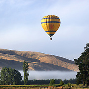 Ballooning over the Hawkes Bay region of the North Island of New Zealand. as the mist sits in the valley at dawn. The flights provide pristine views and spectacular scenery of the surrounding wine region and mountain background at dawn. Early Morning Balloons operates out of Hastings and is run by owners Andrew and Sally Livingston, Rosser Road, Hastings. Hawkes Bay. New Zealand. 12th January 2010 Photo Tim Clayton..