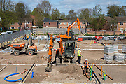 Builders use orange JCBs to lay drainage pipes in the ground around the foundations of a new build housing construction site in Norwich, Norfolk.  United Kingdom (photo by Andrew Aitchison / In pictures via Getty Images)