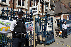 © Licensed to London News Pictures. 11/06/2015. London, UK. A police officer stands outside a polling station in Brick Lane, Tower Hamlets, east London. Tower Hamlets residents go to the polls today to vote for a new Mayor of Tower Hamlets after Lutfur Rahman was removed from office for fraud and corrupt practices by an election court earlier this year. Photo credit : Vickie Flores/LNP