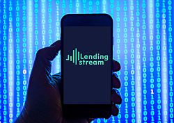 Person holding smart phone with  Lending Stream crowd funding logo displayed on the screen. EDITORIAL USE ONLY