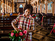 23 DECEMBER 2018 - CHANTABURI, THAILAND:  A volunteer puts flowers on the pews in the Cathedral of the Immaculate Conception in Chantaburi. It is the largest Catholic church in Thailand and was founded more than 300 years ago by Vietnamese Catholics who emigrated to Thailand. The current cathedral building was sited and construction started while Chantaburi was occupied by French forces that had occupied neighboring Cambodia. The cathedral was finished after the French were expelled from Thailand. Chantaburi is the capital city of Chantaburi province on the Chantaburi River. Because of its relatively well preserved tradition architecture and internationally famous gem market, Chantaburi is a popular weekend destination for Thai tourists.   PHOTO BY JACK KURTZ