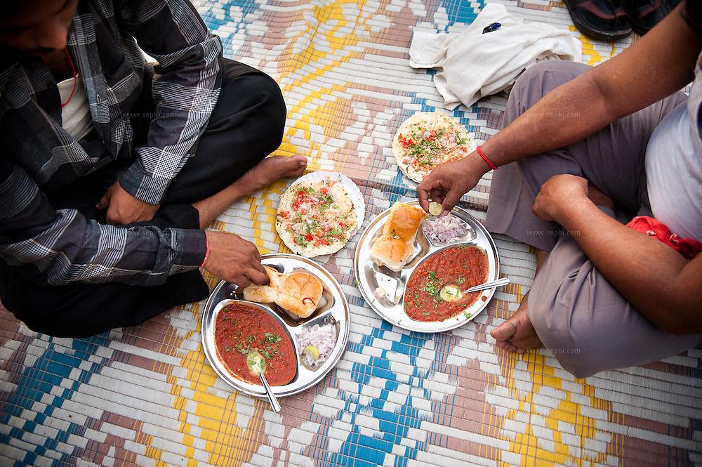 People enjoy Pao Bhaji, a favorite Mumbai snack, while sitting on a mat on the ground at Chowpati beach. Mumbai, August 2009