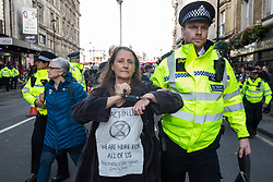 London, UK. 16 October, 2019. Police officers arrest a climate activist from Extinction Rebellion who had defied the Metropolitan Police prohibition on Extinction Rebellion Autumn Uprising protests throughout London under Section 14 of the Public Order Act 1986 by sitting in the road in Whitehall.