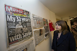 © licensed to London News Pictures. London, UK 24/10/2012. A spectator looking at newspaper cuttings at 'Jimmy Savile is innocent' exhibition at Bread and Butter Gallery in Islington. Photo credit: Tolga Akmen/LNP