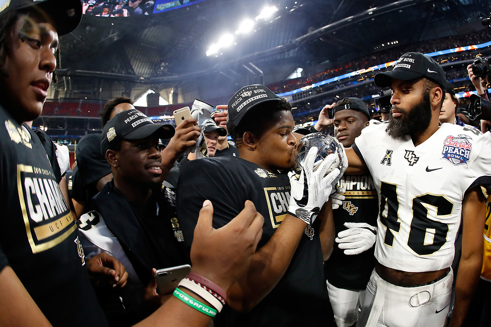 The UCF Knights celebrate beating the Auburn Tigers during the 2018 Chick-fil-A Peach Bowl NCAA football game on Monday, January 1, 2018 in Atlanta. The UCF Knights won 34-27. (Paul Abell / Abell Images for the Chick-fil-A Peach Bowl)