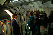 "During the morning rush-hour at Bank underground station in the heart of London's financial district, the grim face of 90s tube travel is seen here in a wide landscape of rounded tunnel and the curve of the station platform. A train guard watches for a green signal as Londoners are sandwiched inside the nearest carriage. Waiting for the doors to close and the hot air to seal them inside the small space, men and women press against each other in a claustrophobic journey along the Central Line. The Central line is a London Underground line, coloured red on the tube map. It is a deep-level ""tube"" line, running east-west across London, and, at 76 km (47 mi). Incorporated in 1891 it is today the longest Underground line and also the busiest with around 260 million passengers a year."