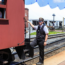 Strasburg, PA – June 18, 2016: A train conductor at the train station with Thomas the Tank Engine.