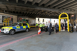 © Licensed to London News Pictures. 10/04/2017. LONDON, UK.  Police, security bollards and cages outside London Bridge station near Southwark Cathedral in London, where a full police funeral takes place this afternoon for PC Keith Palmer. <br /> PC Keith Palmer was stabbed to death whilst on duty in Westminster by terrorist extremist Khalid Masood last month..  Photo credit: Vickie Flores/LNP