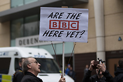 "© Licensed to London News Pictures . 24/03/2018. Birmingham, UK. A man holds a placard reading "" Are the BBC here yet "" at a Football Lads Alliance demonstration against Islam and extremism in Birmingham City Centre . Offshoot group, The True Democratic Football Lads Alliance, also hold a separate demonstration . Photo credit: Joel Goodman/LNP"