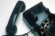A black rotary telephone with the receiver off the hook