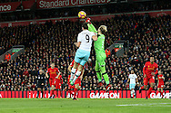 Liverpool Goalkeeper Loris Karius punches the ball clear under pressure from Andy Carroll of West Ham United. Premier League match, Liverpool v West Ham Utd at the Anfield stadium in Liverpool, Merseyside on Sunday 11th December 2016.<br /> pic by Chris Stading, Andrew Orchard sports photography.