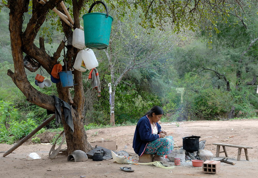Miriam Corremango, a local artisan, works beside the fire in Naurenda, an indigenous community in the Chaco region of Bolivia.