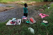A young girl washes the families laundry on a poluted stream that runs down the center of Guaimaca.  Honduras is considered the third poorest country in the Western Hemisphere (Haiti, Nicaragua). With over 50% of the population living below the poverty line and 28% unemployed, Hondurans frequently turn to illegal immigration as a solution to their desperate situation. The Department of Homeland Security has noted an 95% increase in illegal immigrants coming from Honduras between 2000 and 2009, the largest increase of any country.