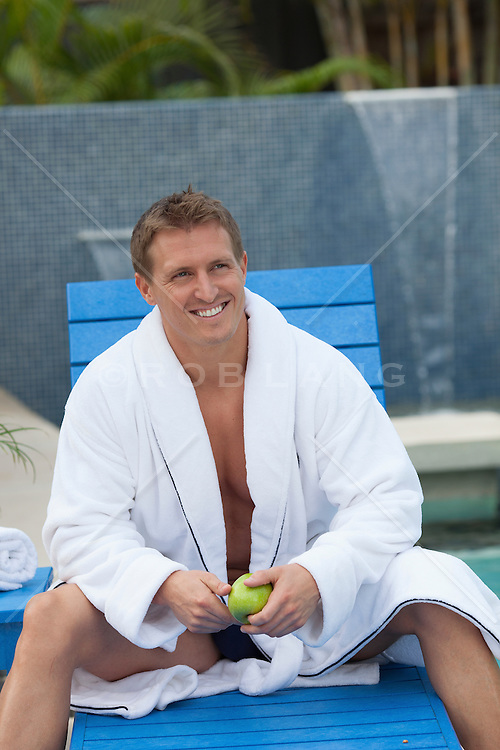 All American man in a white robe at spa by a swimming pool in Florida