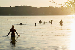 Mature woman walks in lake during sunset and her friends swimming, Bavaria, Germany