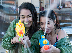 """© Licensed to London News Pictures. 03/06/2015. Bristol, UK.  Giant water fight in Bristol's Millennium Square, organised by The Smile Instigation Collective, a group who say they are dedicated to """"infecting people with happy"""".   It is to celebrate the last session of the Smile Instigation Collective and includes decorating the fountains at Millennium Square with recycled flowers.  Photo credit : Simon Chapman/LNP"""