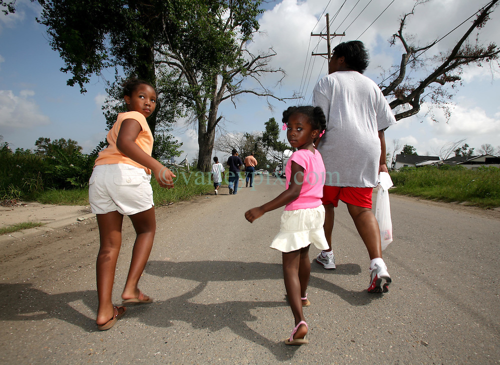 29 August 2006. New Orleans, Louisiana. Lower 9th ward. <br /> Mother Tanya Lewis brings daughters Tanyelle (4yrs) and Kiara (6yrs) back to revisit their devastated former home one year later.  Civilians gathered at the site of the breach of the industrial canal for the Great Flood commemoration and memorial ceremony to 'honor and remember our loved ones who have passed.' People came to mark the anniversary of devastating hurricane Katrina at the site where the now repaired and allegedly in theory stronger levee flood wall. The levee breached along the industrial canal at the point where people gathered, needlessly killing hundreds of innocent civilians in the worst engineering disaster in US history.<br /> Photo Credit©; Charlie Varley/varleypix.com