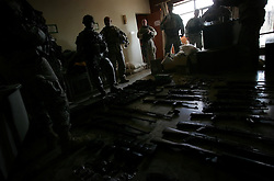 Officers with the 4BN 23rd Infantry Regiment of the 172nd Stryker Brigade tally weapons and supplies stored in the offices of the Iraqi Islamic Party in the Baghdad Sunni neighborhood of Ghazaliyah. The discovery - part of an operation by bolstered US and Iraqi forces in the hopes of getting a handle on the extraordinary numbers of sectarian killings in Baghdad - was carried out in Baghdad, Iraq on Tuesday August 15, 2006. The brigade, which was in the process of rotating home at the end of a year tour in Mosul and northwestern Iraq, was diverted to the capital for an undetermined number of additional months.