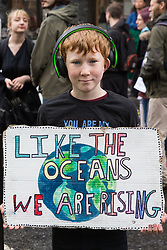 London, UK. 24th April 2019. A young climate change activist from Extinction Rebellion blocks Victoria Street on the tenth day of the International Rebellion to call on the British government to take urgent action to counter climate change.