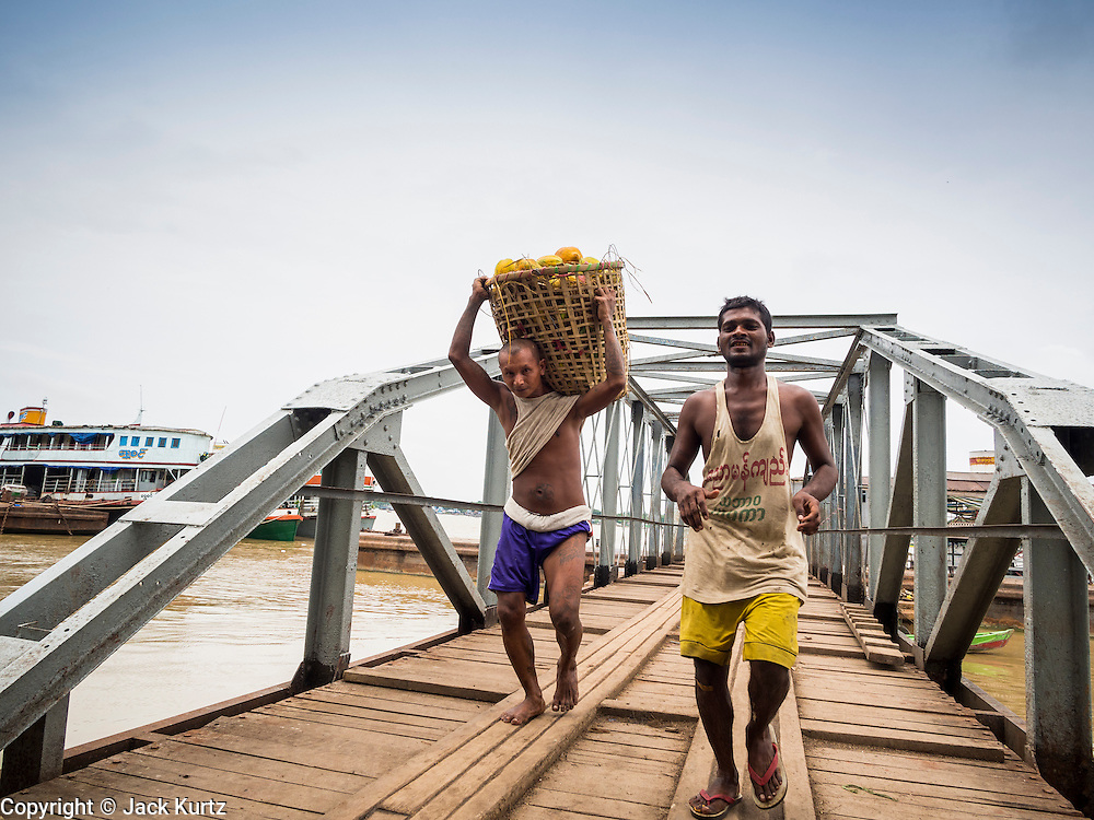 08 JUNE 2014 - YANGON, MYANMAR: Stevedores carry bags of rice to shore from a riverboat on the Yangon waterfront. Yangon, Myanmar (Rangoon, Burma). Yangon, with a population of over five million, continues to be the country's largest city and the most important commercial center.      PHOTO BY JACK KURTZ
