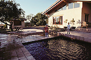 Napa, California. Jack and Evan Menzel look at the wave pattern in the swimming pool and the water that splashed out of the pool at the residence of Peter Menzel a minute after the earthquake that shook their home 107 miles from the epicenter of the October 17, 1989 Loma Prieta Earthquake. At a magnitude of 7.1, it was the worst earthquake in the San Francisco Bay Area since 1906. MODEL RELEASED..