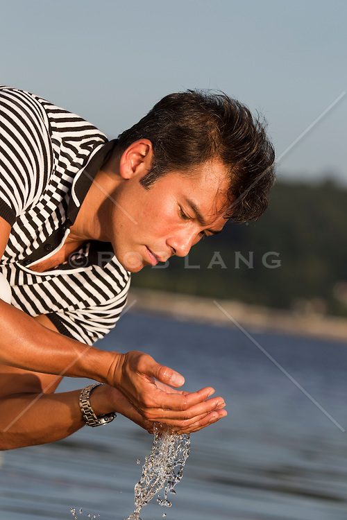 Asian American Man touching the water by the water