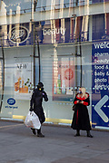 Woman wearing a face mask with a man in full protective gear on Oxford Street, closed for business. March 24th 2020 was the first day of enforced lockdown in the UK, in order to stop the spread of the Coronavirus Covid 19. On what would normally be a bustling business / week day in London, the city was deserted, with just a few people in masks out on the street, plus a few taxis and mostly empty buses.