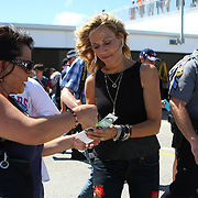Singer Sheryl Crow signs autographs for a fan after a press conference, prior to her performance at the NASCAR Coke Zero 400 Sprint series auto race at the Daytona International Speedway on Saturday, July 6, 2013 in Daytona Beach, Florida.  (AP Photo/Alex Menendez)