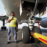 A Bahrani aircraft mechanic stands beneath the giant nose wheel assembly of a Being airliner at Bahrain International Airport. Wearing a red headset, he can communicate by cable with the pilots high up in the aircraft's cockpit as a vehicle pushes-back the flying machine onto the taxi-way before starting its engines and departure. It is another hot day in this Gulf State, a key hub airport in the region, providing a gateway to the Northern Gulf. The airport is the major hub for Gulf Air which provides 52% of overall movements. It is also the half-way point between Western Europe and Asian destinations such as Hong Kong and Beijing. Picture from the 'Plane Pictures' project, a celebration of aviation aesthetics and flying culture, 100 years after the Wright brothers first 12 seconds/120 feet powered flight at Kitty Hawk,1903.